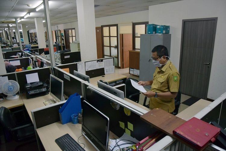 Seorang pegawai negeri sipil (PNS) Pemprov Riau mengenakan masker saat mendapat giliran masuk bekerja di Dinas Komunikasi Informatika dan Statistik Riau.  Sumber: ANTARA FOTO/FB Anggoro