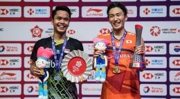 Potret Momota dan Ginting saat naik podium pada ajang BWF World 2019 yang bertempat di China (sumber: bola.com)