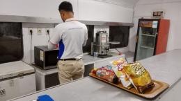 Seorang prama memasak makanan di dalam kereta restorasi KA Lokal. Sebuah hal yang jarang terjadi pada perjalanan kereta api selama ini. - Dokpri