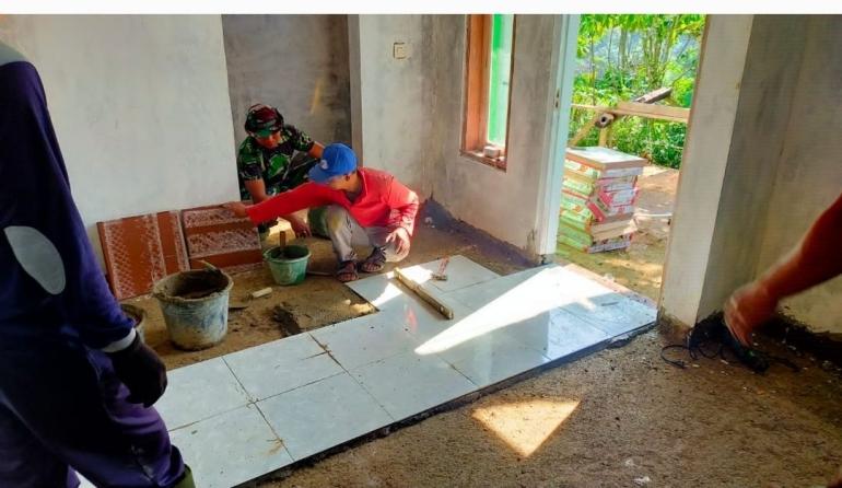 Prajurit TNI Satgas TMMD dengan warga, sedang memasang keramik di rumah pk Tarman/Dokpri