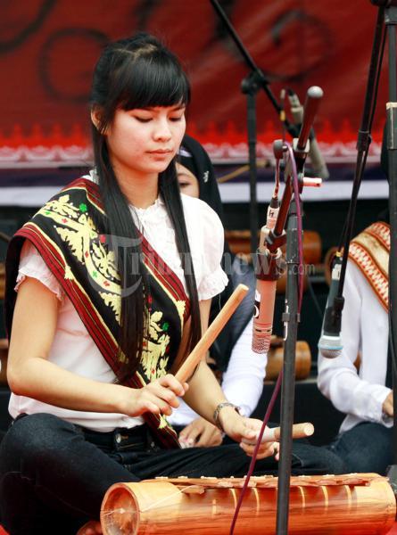 Mahasiswi Program studi Tari Universitas Lampung memainkan alat musik asli Lampung Gamolan di Lapangan Korpri Rabu (7/12). Pemprov Lampung menggelar acara pemecahan rekor museum rekor Indonesia (MURI) tabuh gamolan Lampung,Pemecahan rekor akan dilakukan dengan menabuh gamolan selama 25 jam oleh 25 grup yang terdiri dari 25 penabuh. Sumber: TRIBUNNEWS.COM/Perdiansyah
