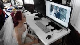 Mulan Jameela sedang duduk di depan komputer, melihat hasil dari syuting.