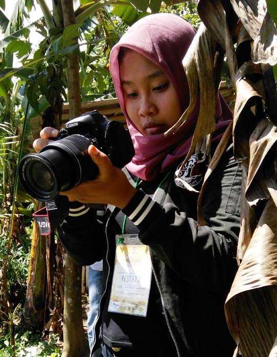 Salah seorang peserta Lomba Fotografi diantara pepohonan mencari posisi bidikan tepat. (Foto: Gapey Sandy)