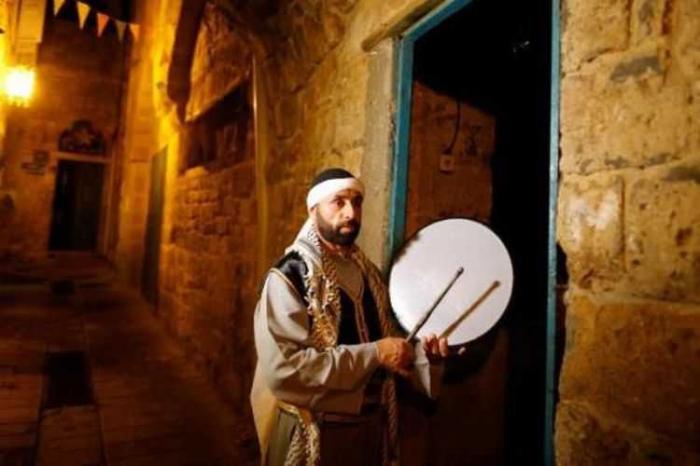 Seorang warga membangunkan sahur. Foto dari kompas.com