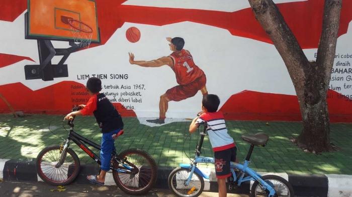 Petra dan Hafiz sedang memandangi mural legenda basket Indonesia, Liem Tjien Song (dok. pri).