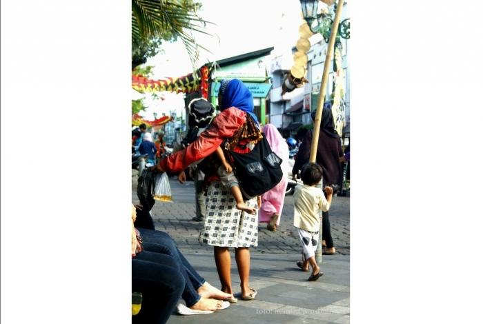 Seorang peminta-minta dengan anak kecil berjalan di kawasan Malioboro Yogyakarta (dok. pri).