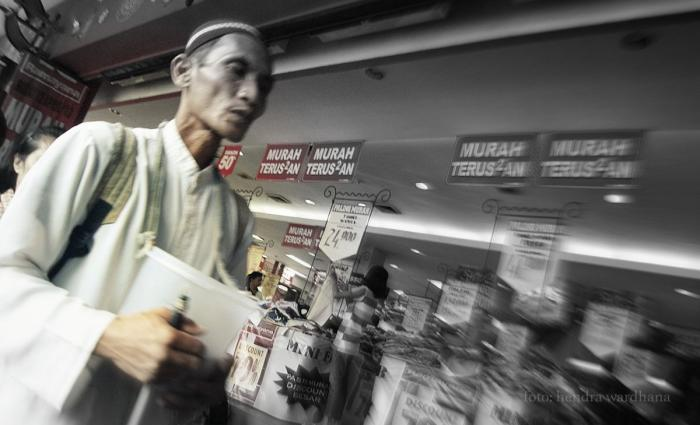 Seorang peminta-minta berjalan di depan pusat perbelanjaan (dok. pri).