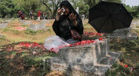 Seorang ibu berziarah di makam korban tragedi mei 98.foto : tempo/Muhammad hidayat