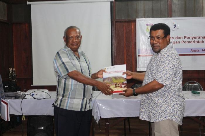Guru Felix menerima buku kegiatan LANDASAN Papua dari Septer Manufandu. Dokpri.