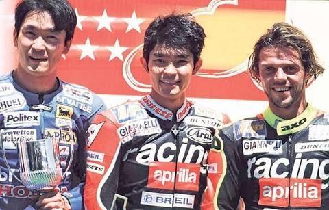 Tetsuya Harada (tengah) dan Loris Capirossi (kanan) saat membela Aprilia. Mereka pernah terlibat insiden kontroversial di seri terakhir GP250 tahun 1998 dimana Capirossi menyerempet Harada di tikungan terakhir saat memperebutkan posisi pertama dengan Valentino Rossi | Foto motorcyclenews.com