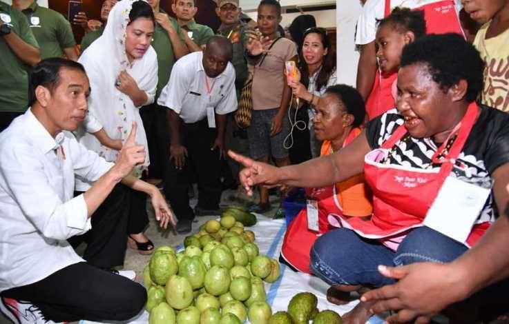Presiden Joko Widodo didampingi Ibu Negara, Iriana Widodo, membeli jambu di Pasar Mama-mama, Papua. Mari kita rangkul saudara-saudara kita dari Papua, untuk bersama-sama berkontribusi pada bangsa ini. Foto: Biro Pers Media Kepresidenan/Agus Suparto dari beritasatu.com