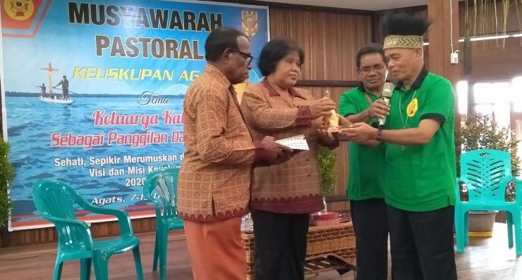 Mgr. Aloysius Murwito OFM menyerahkan cenderamata kepada pasangan keluarga yang memberi kesaksian pada pelaksanaan Musyawarah Pastoral ke-5 Keuskupan Agats, 7-13 Oktober 2019. Dokpri.