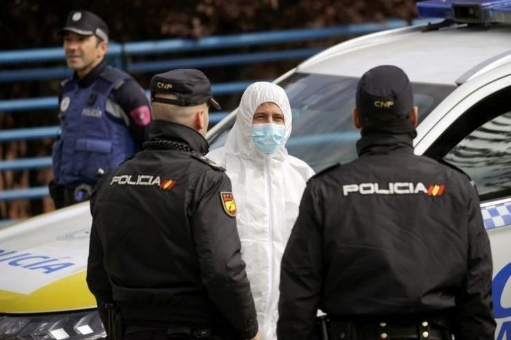 Seorang anggota dari militer Spanyol berbicara dengan dua polisi di Madrid, pada 24 Maret 2020, di tengah wabah virus corona.(REUTERS/JUAN MEDINA)