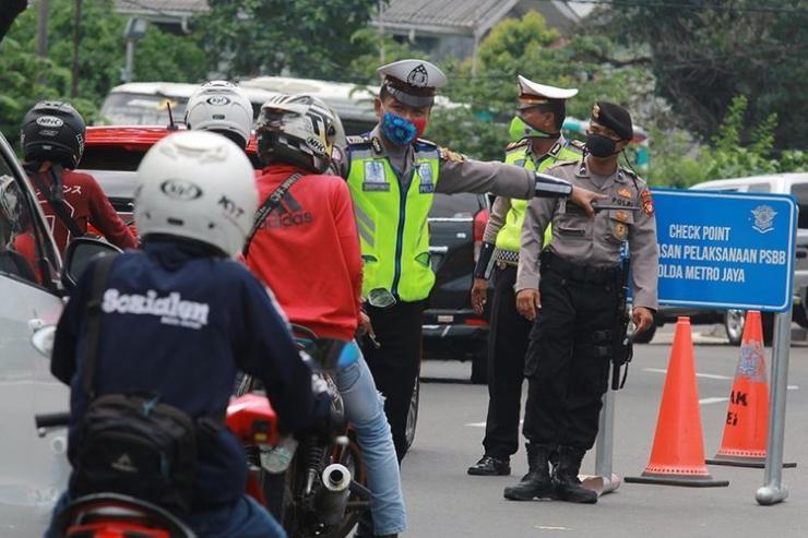 Polisi menghalau pengendara tak bermasker yang hendak masuk ke Jakarta selama PSBB. Foto: KOMPAS.com/Antara