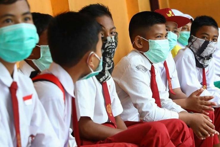 Siswa sekolah dasar di Natuna, Kepulauan Riau, mengenakan masker saat berada di area sekolah mereka, Selasa (4/2/2020). (AFP/RICKY PRAKOSO via KOMPAS.com)