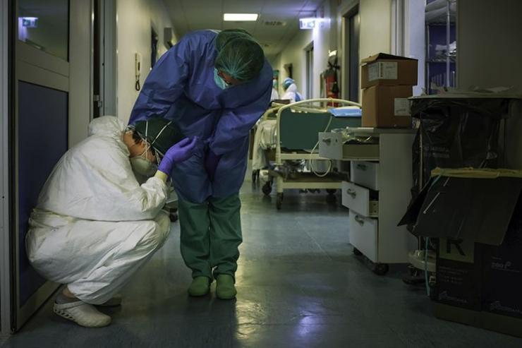Seorang perawat berupaya menenangkan rekannya saat pergantian shift mereka di Rumah Sakit Cremona, tenggara Milan, Lombardy, Italia, Jumat (13/3/2020). Selama diberlakukannya lockdown di Italia terkait meledaknya penyebaran virus corona di negara tersebut, sosok para tenaga medis banjir dukungan atas dedikasi mereka yang menjadi pahlawan dalam menangani serbuan pasien corona.(AFP/PAOLO MIRANDA via KOMPAS.com)