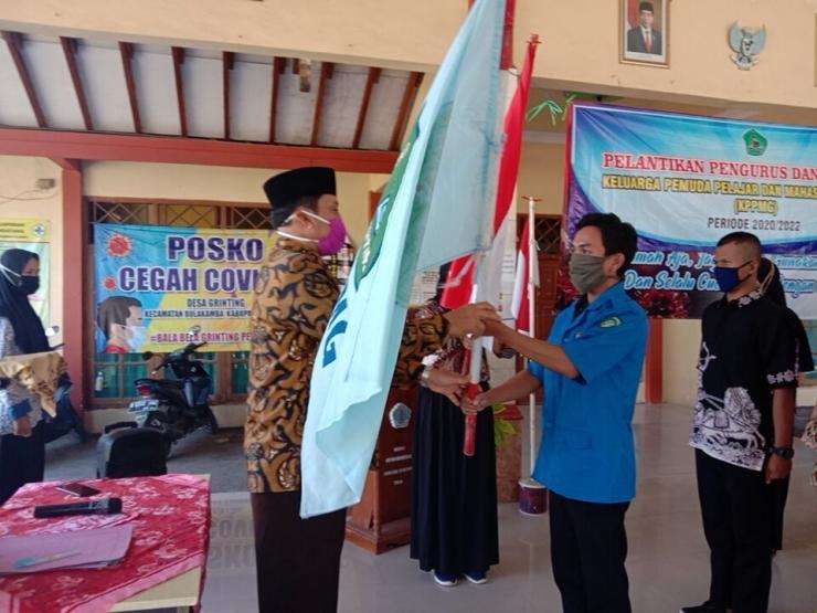 Kepala Desa Grinting, Suhartono S.H., M.H. menyerahkan bendera KPPMG kepada ketua yang baru|Dokpri