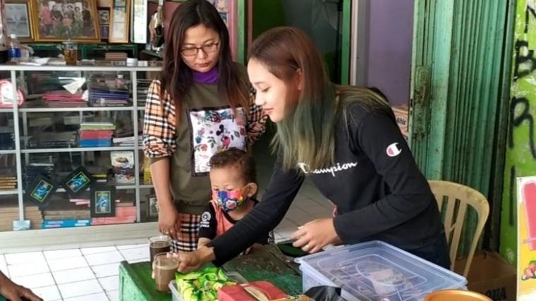 Melani saat melayani penikmat kopi yang sebagian adalah para sopir angkot diterminal. (FOTO:Cokie)