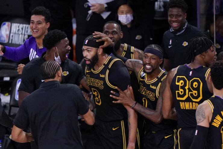 Los Angeles Lakers, Anthony Davis (tengah), dikerumuni rekan-rekannya setelah mencetak lemparan tiga angka penentu kemenangan Lakers atas Denver Nuggets pada gim kedua Final Wilayah Barat NBA di Lake Buena Vista, Florida, Senin (21/9/2020) pagi WIB. (Foto: KEVIN C. COX/GETTY IMAGES/AFP)
