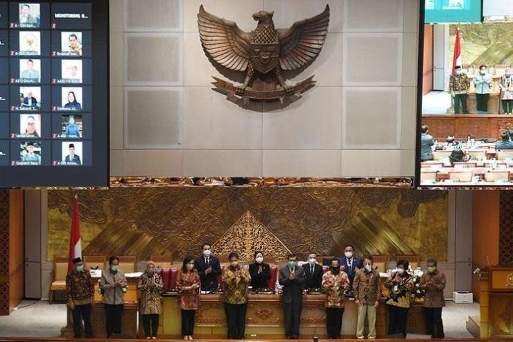 Menko Perekonomian Airlangga Hartarto (kelima kiri) bersama Menkumham Yasonna Laoly (kelima kanan), Menteri Keuangan Sri Mulyani (keempat kiri), Mendagri Tito Karnavian (keempat kanan), Menaker Ida Fauziyah (ketiga kiri), Menteri ESDM Arifin Tasrif (ketiga kanan), Menteri ATR/Kepala BPN Sofyan Djalil (kedua kiri) dan Menteri LHK Siti Nurbaya (kedua kanan) berfoto bersama dengan pimpinan DPR usai pengesahan UU Cipta Kerja pada Rapat Paripurna di Kompleks Parlemen, Senayan, Jakarta, Senin (5/10/2020). Dalam rapat paripurna tersebut Rancangan Undang-Undang Cipta Kerja disahkan menjadi Undang-Undang | ANTARA FOTO/HAFIDZ MUBARAK/Kompas.com.