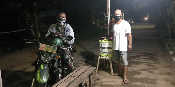 Bapak Agustusin Roba'I (Ketua RW desa Kalisuren) bersama salah satu anggota TNI di pos kesehatan untuk pengecekan suhu dan penyemprotan disinfektan. (Dokpri)