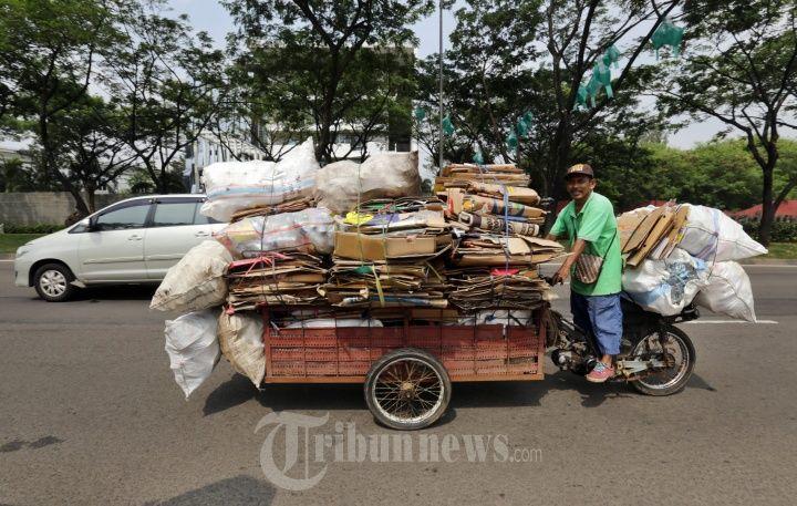 Seorang pemulung dengan sepeda motor yang sudah dimodifikasi menjadi gerobak melintas di Jalan Boulevard BSD Timur, Tangerang Selatan pada Jumat (22/6/2018)| Sumber: Warta Kota/Alex Suban via Tribunnews.com