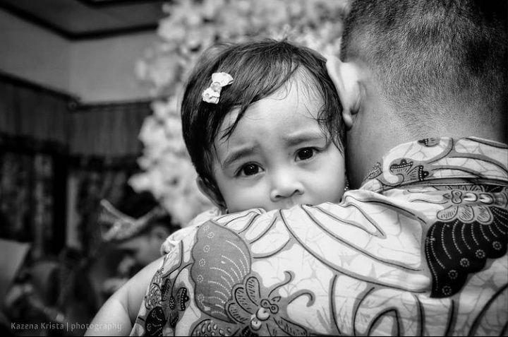 Seorang Ayah menggendong anak perempuannya. (Foto oleh Kazena Krista)