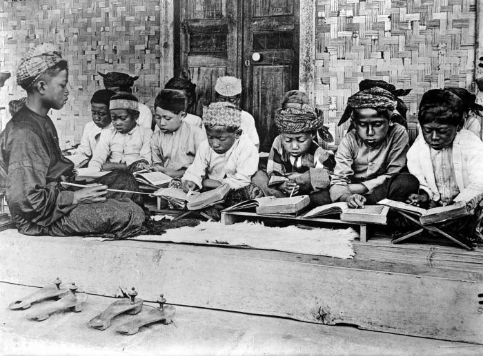 A photo taken in a Javanese madrassah in the Dutch Colonial period. Left hand corner of the picture shows two pairs of wooden Javanese clogs. In Cape Town, these were called kaparangs and could be found in many old masjids in cape town. Also notice the manner of teaching and learning the holy Quran, using a 'kalam' (wooden stick) to point. this method still used in many old-school madrassahs in cape town. Also the usage of melayu terms for arabic vowels - fat'ha = dettis (di atas), Kasrah = bawah, Dommah = dapan, tanween = dua dettis, dua dapan, dua bawah, Shaddah = saptu (Sumber: https://www.sites.google.com/site/aljaamiahacademy)