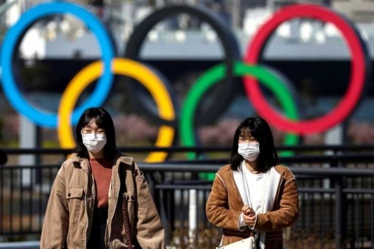 Dua warga berjalan di depan logo olimpiade di Tokyo, Jepang.(REUTERS via ABC INDONESIA/KOMPAS.COM)