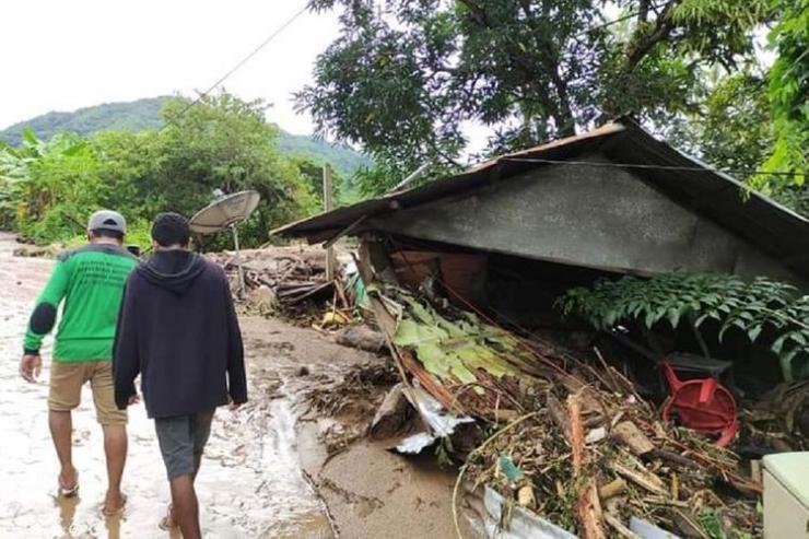 Warga melintas di dekat rumah yang rusak akibat banjir bandang di Adonara Timur, Flores Timur, NTT, Senin (5/4/2021). Berdasarkan data BNPB hingga senin siang, korban meninggal dunia akibat banjir bandang di Flores Timur mencapai 68 jiwa (ANTARA FOTO/PION RATULOLI)